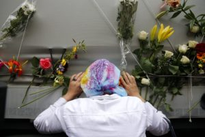epa04838257 A Bosnian woman pays her respects to the remains of 136 identified Bosnian Muslims ahead of the burial ceremony in Sarajevo, Bosnia and Herzegovina, 09 July 2015. July 2015 marks the 20-year anniversary of the Srebrenica Massacre that saw more than 8,000 Bosnians men and boys killed by Bosnian Serb forces during the Bosnian war.  EPA/VALDRIN XHEMAJ